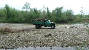Zbieranie dreva a kameniva na brehu rieky Bystricja.